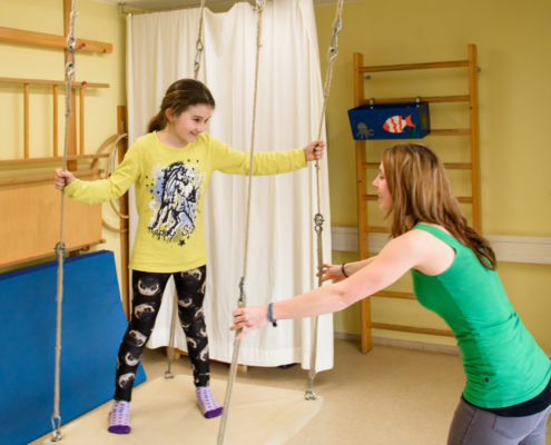 Kind auf Schaukel mit Therapeutin